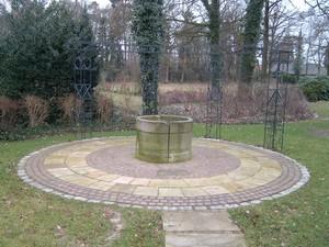 Sandsteinbrunnen mit Rosenrankbogen